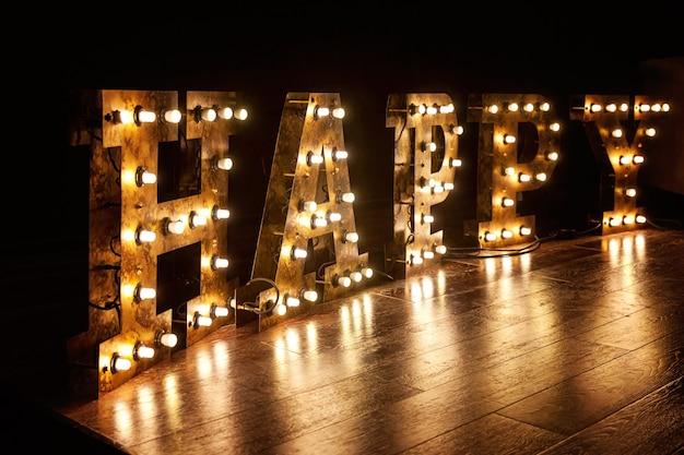 Glühende retro-glühbirnen des glücklichen buchstabenwortes mit retro-lampenlicht