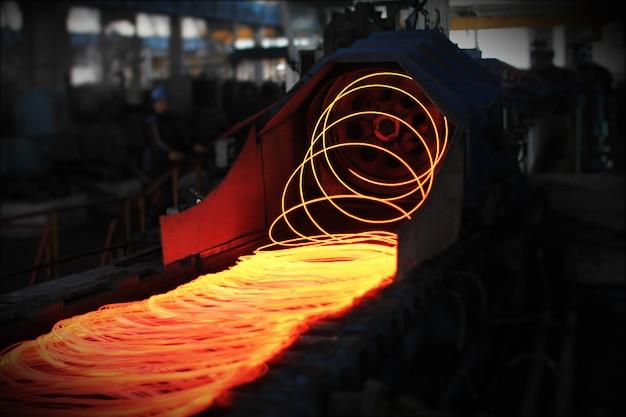 Glühende stahlmetalldrahtstangen oder -spulen nach dem gießen von geschmolzenem stahl. stranggießmaschine. hintergrund der schmiede- und metallurgieindustrie.