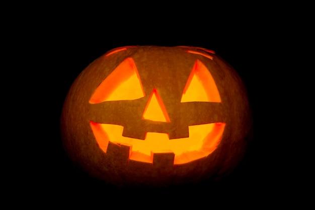 Glühende unheimliche halloween-kürbislaterne auf schwarzem hintergrund.