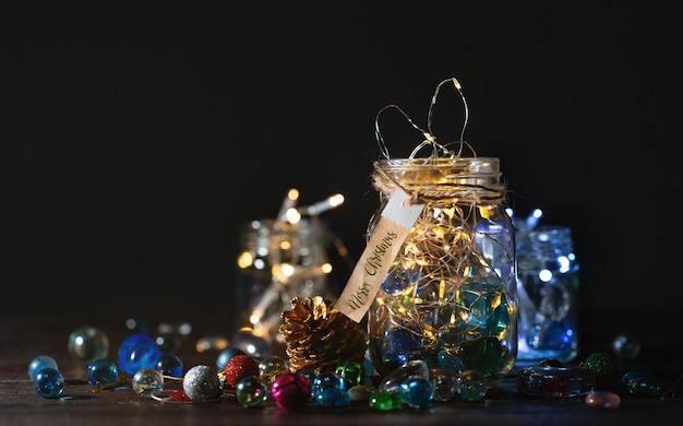 Glühende weihnachtslichter und goldener kiefernkegel in einem glasgefäß, weihnachtsdekorationshintergrund.