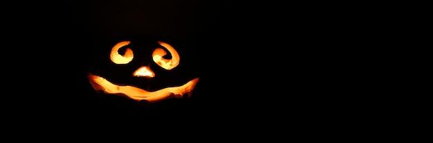 Glühender lächelnder gesicht-halloween-kürbis, kerzenhalter, lokalisiert auf dunklem schwarzem hintergrund der nacht. platz für text.