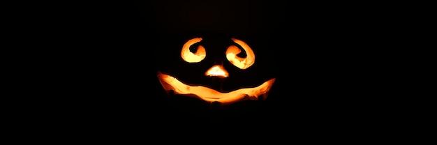 Glühender lächelnder gesicht-halloween-kürbis, kerzenhalter, lokalisiert auf dunklem schwarzem hintergrund der nacht.