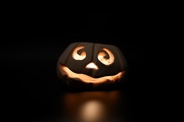 Glühender lächelnder gesicht-halloween-kürbis, kerzenhalter, lokalisiert auf dunklem schwarzen hintergrund der nacht