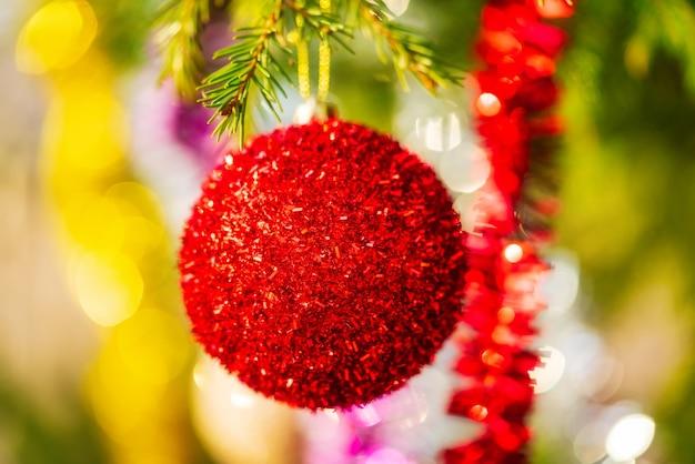 Glühender roter weihnachtsball und bunter leuchtender lametta, der am zweig des baums hängt. nahaufnahme xmas festliche komposition für ein glückliches neues jahr. selektiver fokus im vordergrund, verschwommenes bokeh im hintergrund.