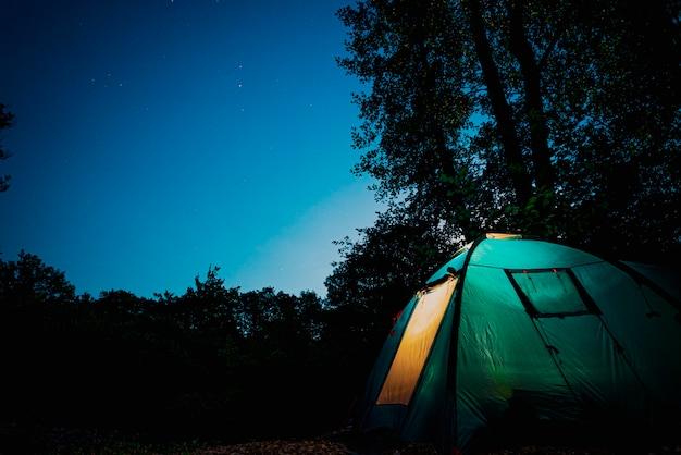 Glühendes blaues zelt im wald unter einem sternenklaren abendhimmel. sonnenuntergang im wald. sommerlandschaft.