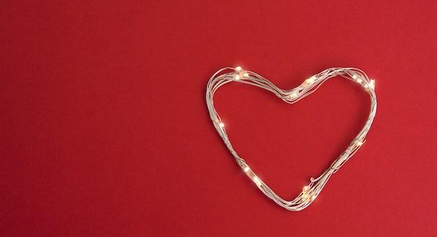 Glühendes girlandenherz auf einem roten backround. kopieren sie platz. leer für banner oder karte zum valentinstag oder hochzeit
