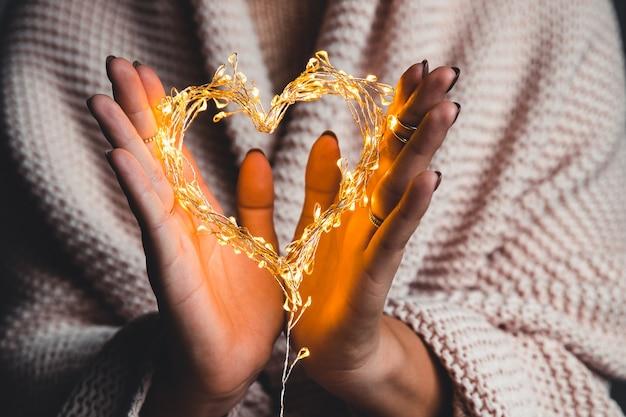 Glühendes herz in den händen einer frau. fröhlichen valentinstag. plaid, komfort, winter, girlandenherz in den händen einer frau. fröhlichen valentinstag