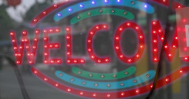 Glühendes schild mit roten lichtern mit aufschrift willkommen auf glastür