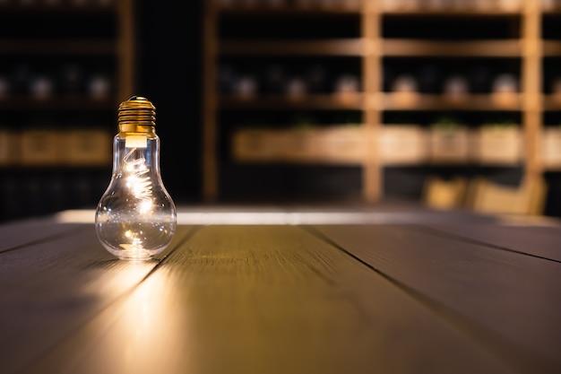 Glühlampe auf hölzerner tabelle