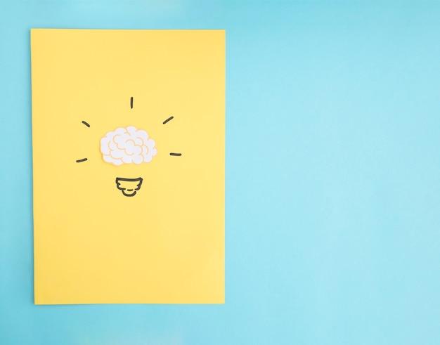 Glühlampe der gehirnidee auf gelbem papier über dem blauen hintergrund