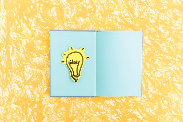 Glühlampe der idee auf blauem seitennotizbuch über dem gelben strukturierten hintergrund