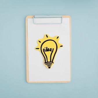 Glühlampe der idee auf weißbuch über dem klemmbrett gegen grauen hintergrund