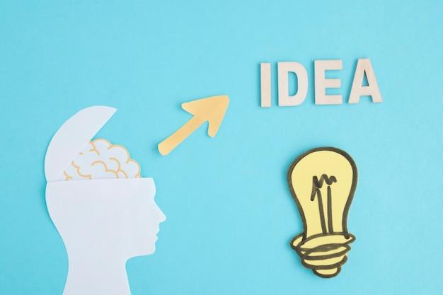 Glühlampe der idee mit offenem gehirnkopf auf blauem hintergrund