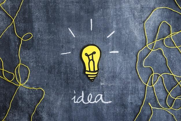 Glühlampe des papierausschnitts mit geschriebenem ideentext und wolle verlegen auf tafel