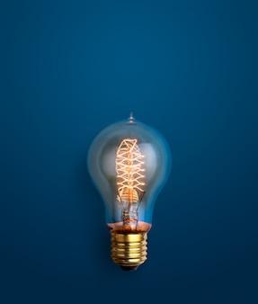 Glühlampe, die auf hintergrundkonzept der kreativen ideen des blauen hintergrundes glüht.