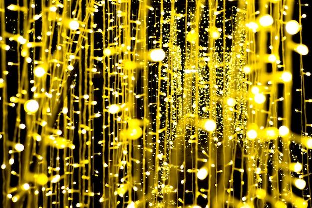 Glühlampe, die einen leuchter hängt, ein kleines, schönes gelbes goldbokeh auf einem schwarzen hintergrund belichtend.