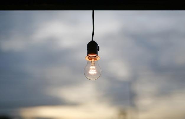 Glühlampe eingeschaltet über hintergrund des bewölkten himmels