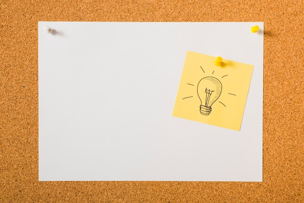 Glühlampe gezeichnete ikone auf gelber klebriger anmerkung über dem anschlagbrett