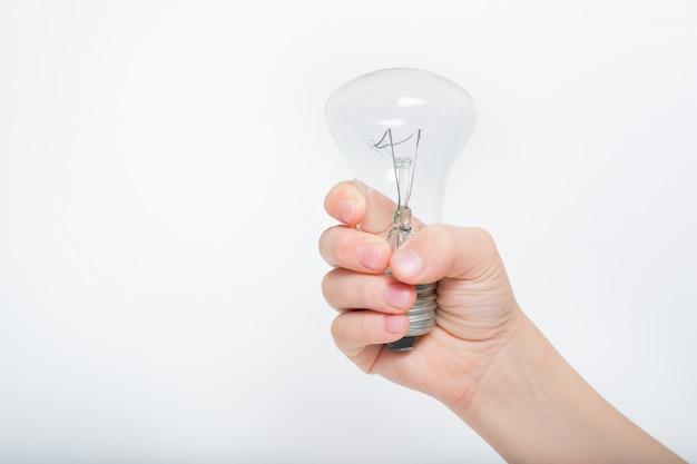 Glühlampe in der hand eines kindes auf einem hellen hintergrund