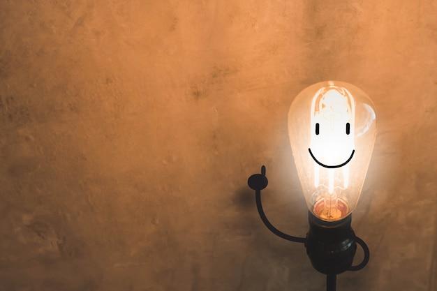 Glühlampe mit lächelngesichtskonzept auf altem betonmauerhintergrund.