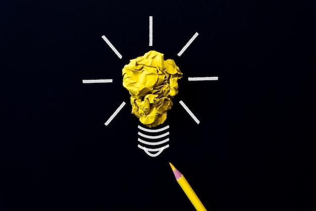 Glühlampe mit zerknittertem buntem papier und gelbem bleistift auf schwarzem hintergrund.