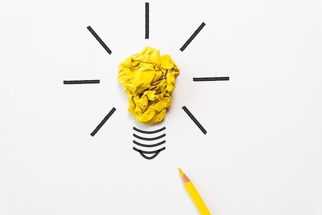 Glühlampe mit zerknittertem buntem papier und gelbem bleistift auf weißem hintergrund.