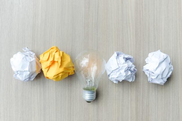 Glühlampe oder lampe mit buntem zerknittertem papier auf holztisch