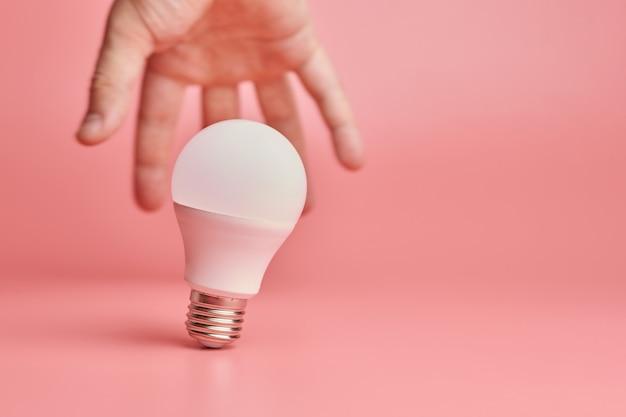 Glühlampe und hand, anziehendes konzept der idee. symbol für neue ereignisse oder das finden von lösungen für probleme.