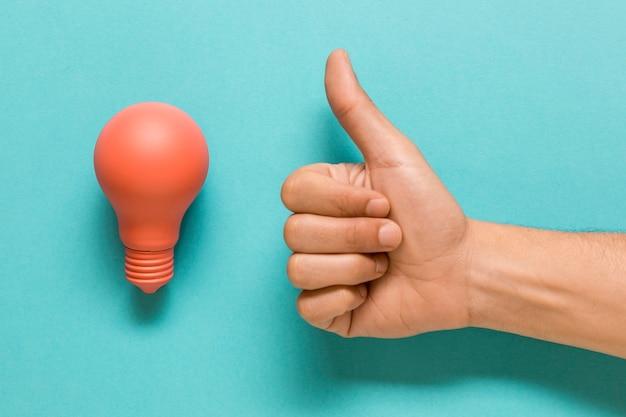 Glühlampe und hand, die sich daumen zeigen