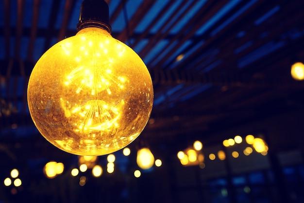 Glühlampen, die von der decke mit dunklem hintergrund hängen