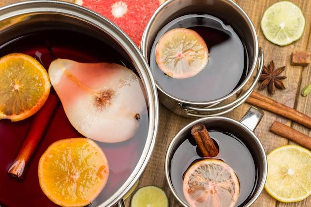 Glühwein aus zitrusfrüchten mit gewürzen in metallbechern und topf