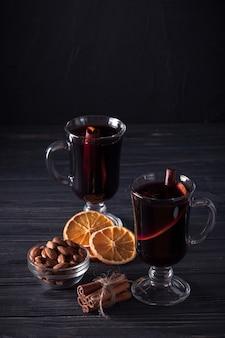 Glühwein-banner. gläser mit heißem rotwein und gewürzen auf dunklem hintergrund. moderner dunkler stimmungsstil.