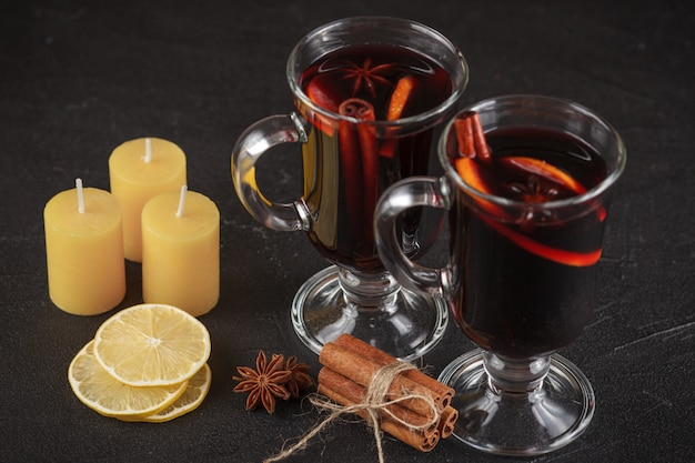 Glühwein-banner. gläser mit heißem rotwein und gewürzen auf dunklem hintergrund.