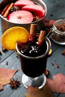 Glühwein. glas heißes wintergetränk mit zitrusfrüchten, apfel und gewürzen.