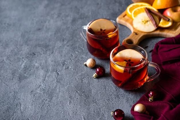 Glühwein-heißgetränk mit zitrusfrüchten, äpfeln und gewürzen auf beton
