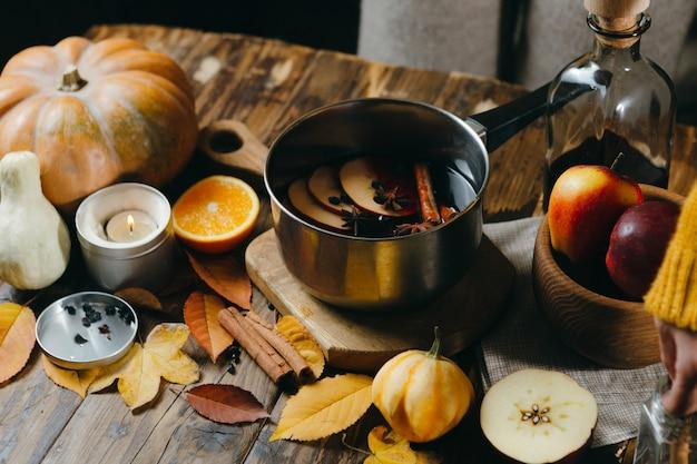 Glühwein-heißgetränk mit zitrusfrüchten, äpfeln und gewürzen im aluminiumtopf auf holz