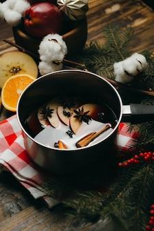 Glühwein-heißgetränk mit zitrusfrüchten, äpfeln und gewürzen im aluminiumtopf auf karierter tischdecke.