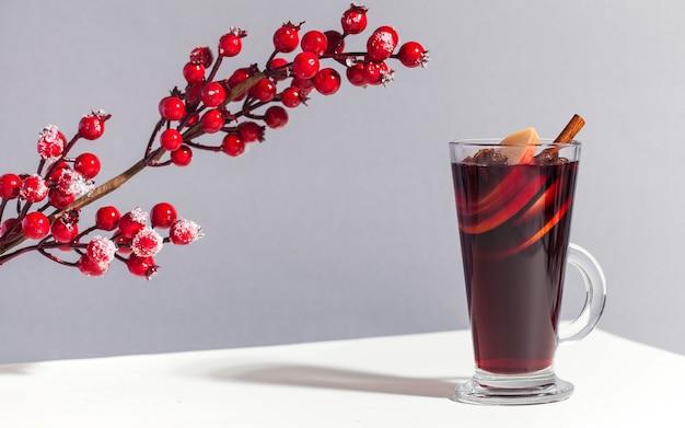 Glühwein im glas mit einer zimtstange mit roten winterbeeren trendig das foto mit...