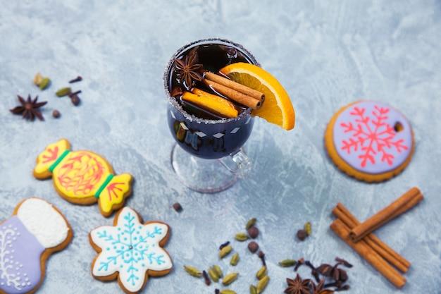 Glühwein im glasbecher mit gewürzen. heißes weihnachtsgetränk mit dekoriertem neujahrs-ingwerbrot auf grauem steintisch. draufsicht.