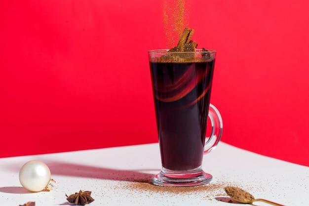 Glühwein in einem glas auf einer roten oberfläche mit einem weihnachtsbaumspielzeug und fallenden goldflitter