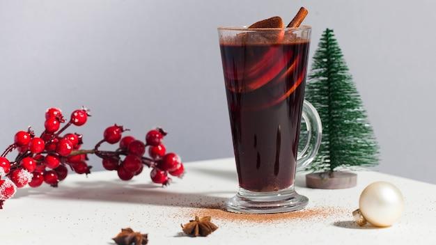 Glühwein in einem glas mit einem weihnachtsbaum ein zweig mit roten beeren des winters fotos bei hartem licht...