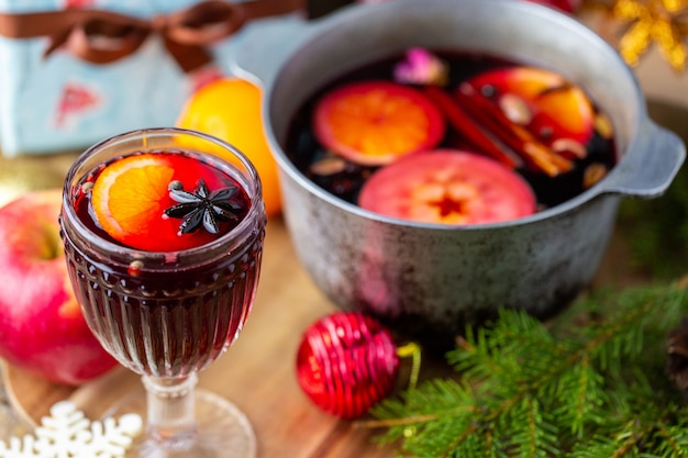 Glühwein in einem schönen glas neben dem topf. heißes getränk in einem glas. weihnachtskonzept. familienabend mit einem heißen getränk.