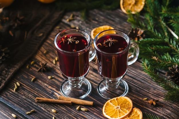 Glühwein in glasgläsern mit orangenscheiben, zimtstangen und gewürzen mit weihnachtsdekor