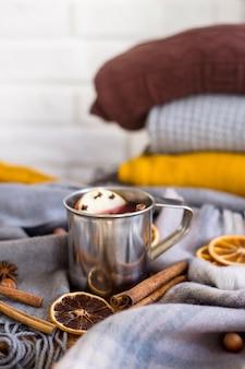 Glühwein mit apfel, orange, nelke, zimt und anis in einem metallbecher