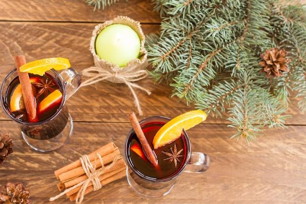 Glühwein mit gewürzen. weihnachtsdekoration mit getrockneten orangenscheiben. zimtstangen und weihnachtsgeschenke auf holzuntergrund