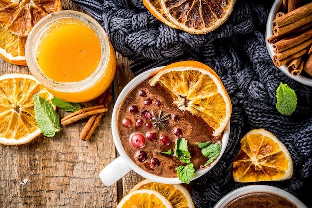 Glühwein mit heißer schokolade, gewürzen, preiselbeeren und getrockneter orange Premium Fotos