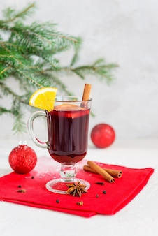 Glühwein mit zimt, anis, nelken und orange in einer tasse mit einem weihnachtsbaum.