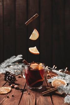 Glühwein weihnachtstasse auf tisch levitation von zimtstange orange apfel
