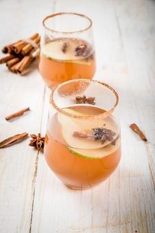Glühwein. würziges cocktail des traditionellen herbstes mit birnen-, apfelwein- und schokoladensirup, mit zimt, anis, braunem zucker. auf einem weißen holztisch.
