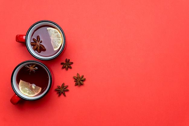 Glühweinpunsch und gewürze für glitzerwein auf minimalem rotem hintergrund